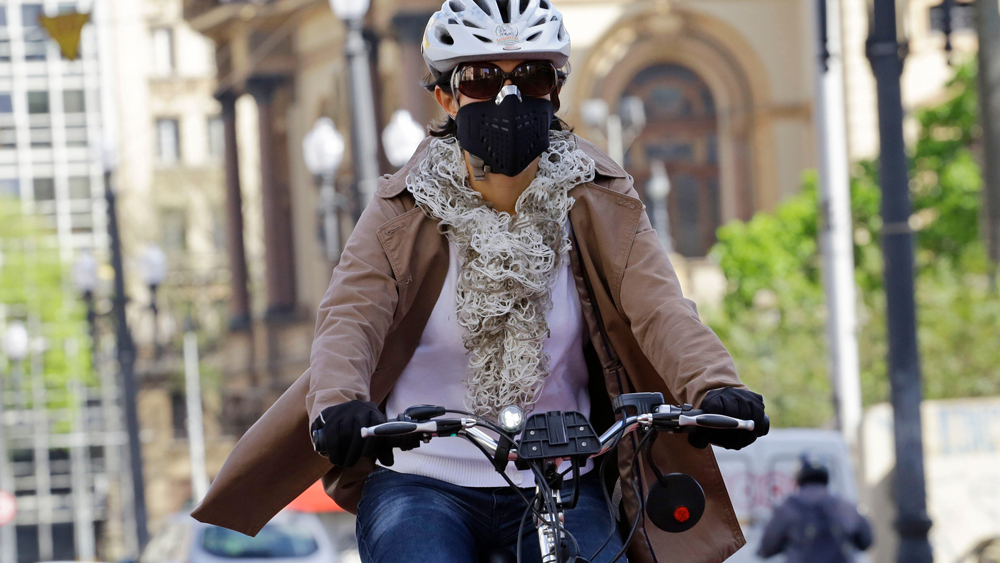Woman cycling wearing a face mask